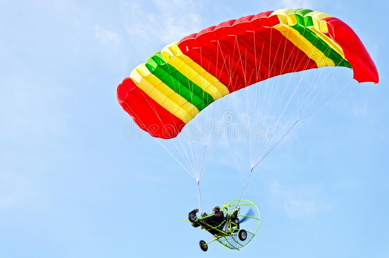 Motorized paraglider up high in blue sky. Man taking flight in his motorized paraglider with brilliant colors stock images