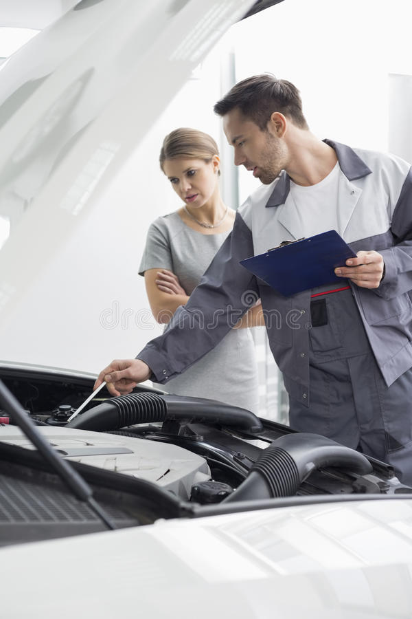 Motorn för bilen för den manliga underhållsteknikern shoppar den förklarande till den kvinnliga kunden i reparation royaltyfria foton