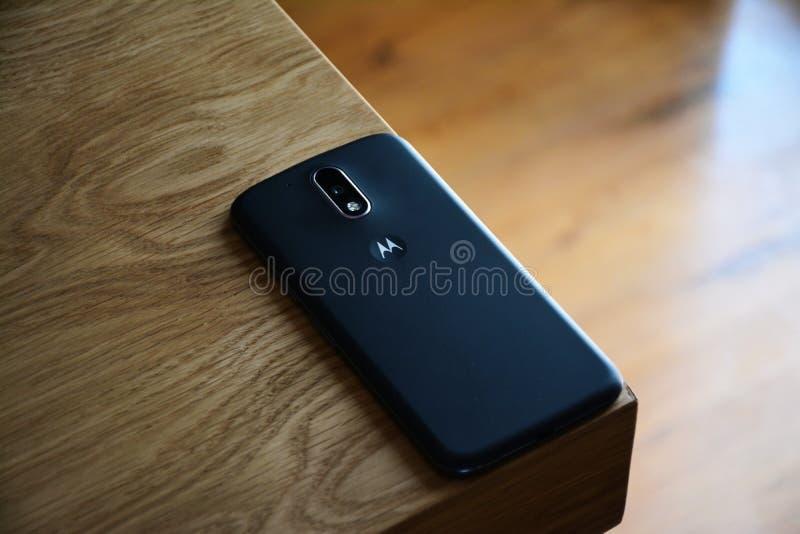 Η μαύρη Motorola Smartphone πάνω από τον καφετή ξύλινο πίνακα στοκ εικόνες