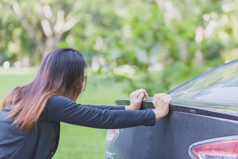 Motoropsplitsing Sterke vrouw die een vuile auto duwen Vervoer, groepswerk, concept stock foto's