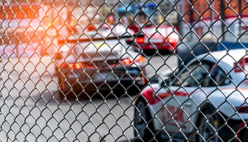 Motorowy sportowy samochód ściga się na asfaltowej drodze Widok od płotowego siatki siatkarstwa na zamazanym samochodzie na toru  obrazy royalty free