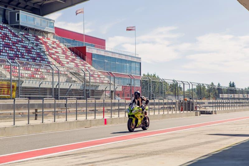 Motorracer in een groene kostuum en helm, die een motorfiets een berijden rond de kuilen aan praktijk stock foto