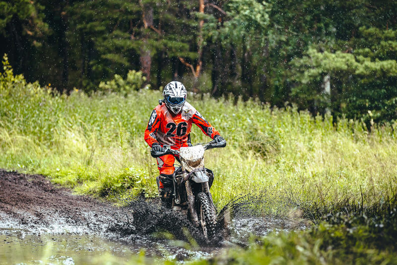 Motorracerritten in een vulklei van modder in hout rond hem waterplonsen stock afbeelding