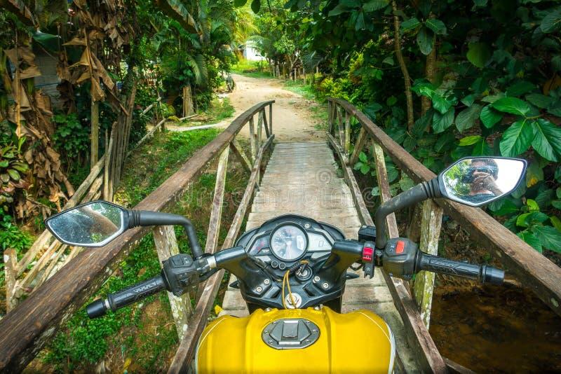 Motorrad, das eine schmale Holzbrücke im Hafen Barton, Palaw kreuzt lizenzfreie stockfotos