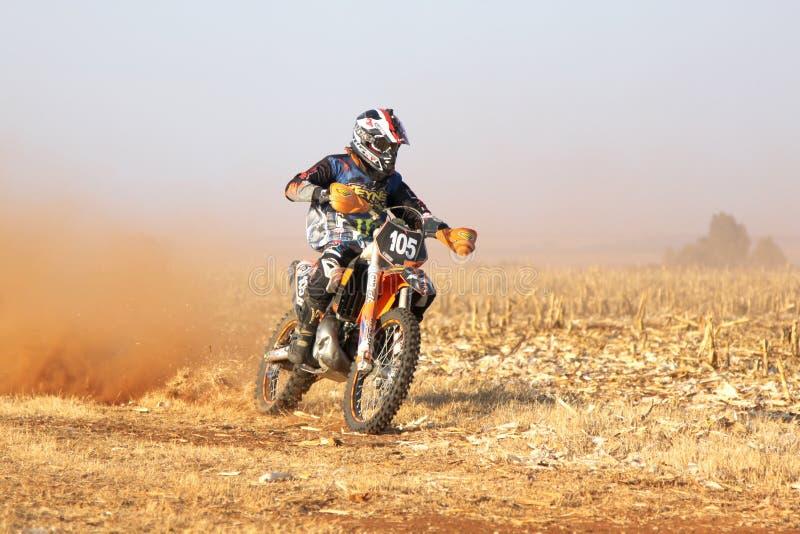 Motorrad, das oben Spur des Staubes auf Sandbahn während des Sammlungsra tritt stockfotografie
