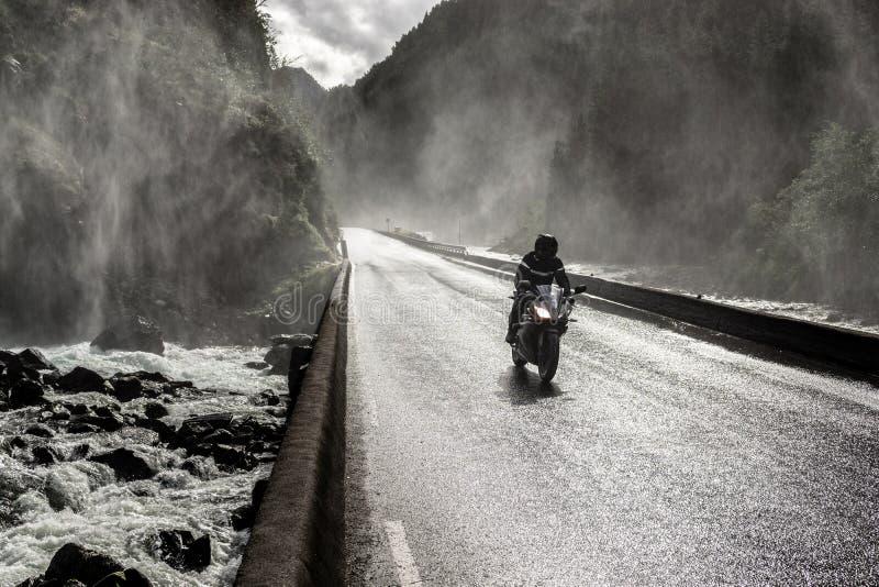 Motorrad, das schnell auf nasse Schluchttalstraße und -brücke über Fluss fährt stockbilder