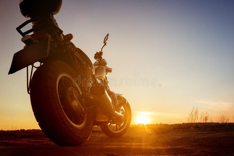 Motorrad steht auf Sonnenunterganghintergrund-Himmelstraße lizenzfreie stockfotografie