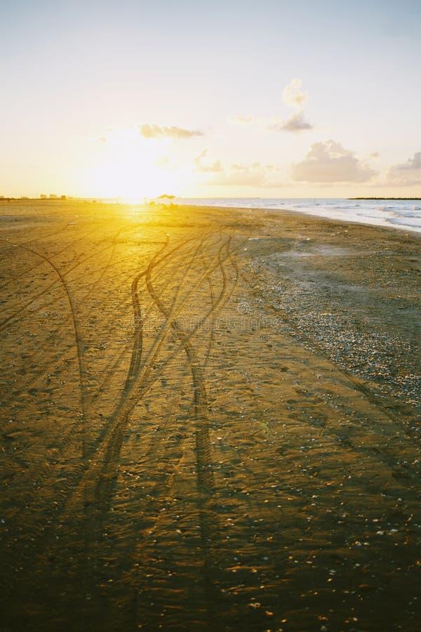 Motorradbahnen im goldenen Strandsand stockbild