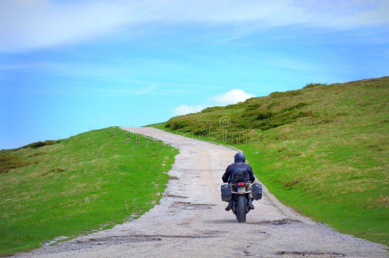 Motorradfahrer auf Gebirgsweg stockbild