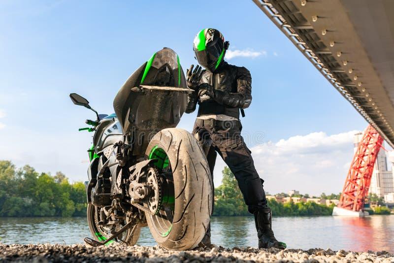 Motorradfahrer in einem Sturzhelm und in einem Schutzanzug steht unter der Brücke stockbild