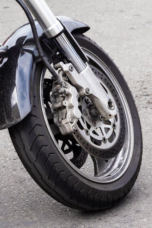 Motorradrad Nahaufnahme des Vorderrads eines Motorrades und der Bremsscheibe Chrome-Gabel und schwarzer Motorradflügel stockbild