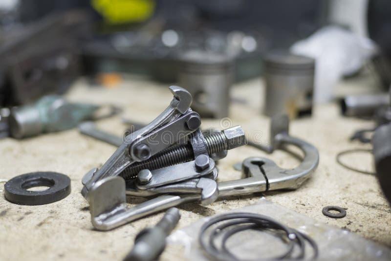 Motorradteile und -werkzeuge auf dem Desktop in der Garage stockfoto