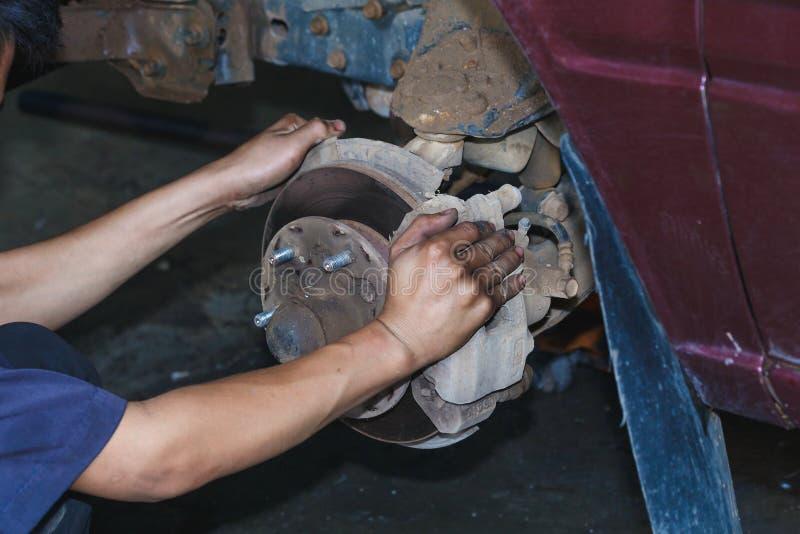 Motorreparatie, Werktuigkundige die in een auto onder de kap werken stock fotografie