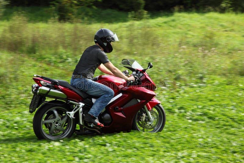 Motorrijder die op weide berijdt royalty-vrije stock foto