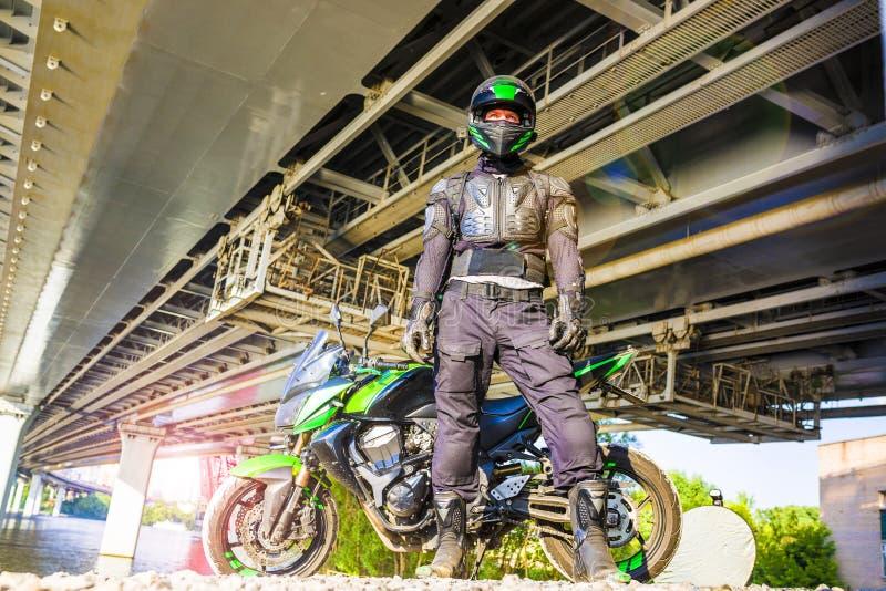 Motorrijder in een helm en in een beschermende kostuumtribunes onder t stock foto's