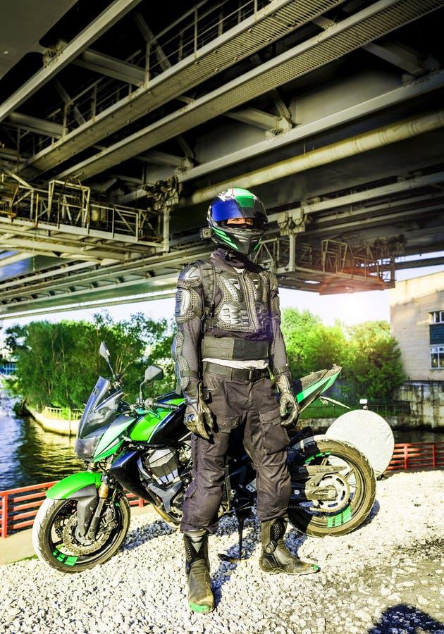 Motorrijder in een helm en in een beschermende kostuumtribunes onder t royalty-vrije stock afbeelding