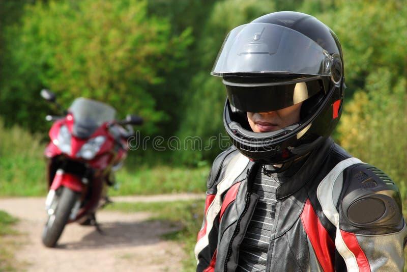 Motorrijder en zijn fiets bij de landweg stock fotografie