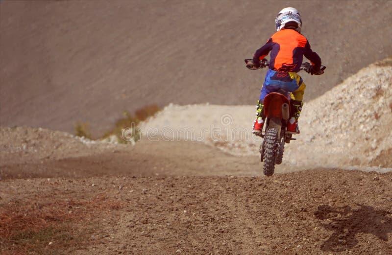 Motorrijder op een motorfiets in het hele land in een sprong royalty-vrije stock foto