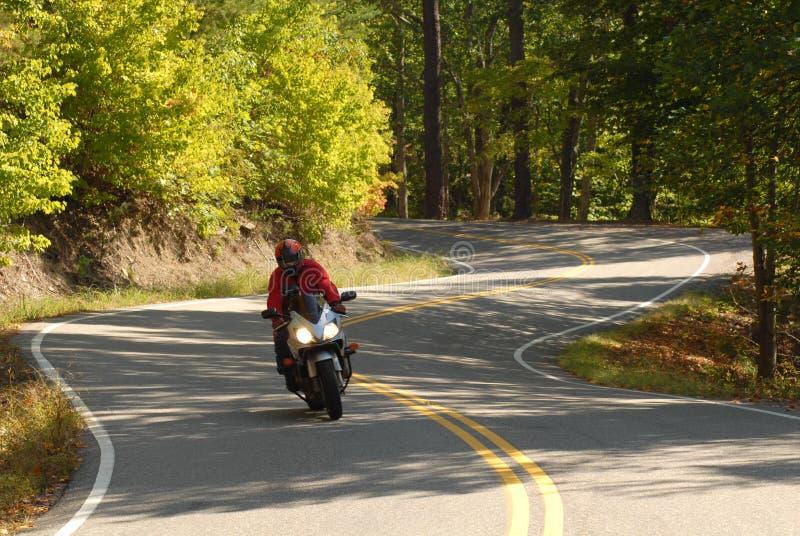 Motorrijder op een windende weg stock fotografie