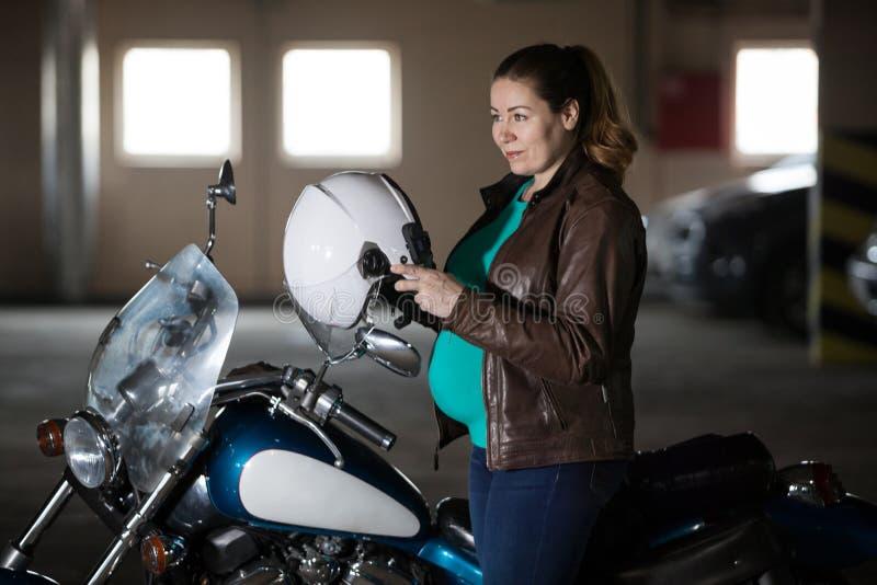 Motorrijder zwangere vrouw die bijlfiets, gezet op helm voorbereidingen treffen te berijden bij parkeerterrein stock fotografie