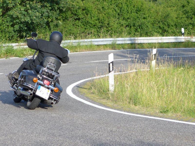 Motorrijderaandrijving door een kromming royalty-vrije stock fotografie