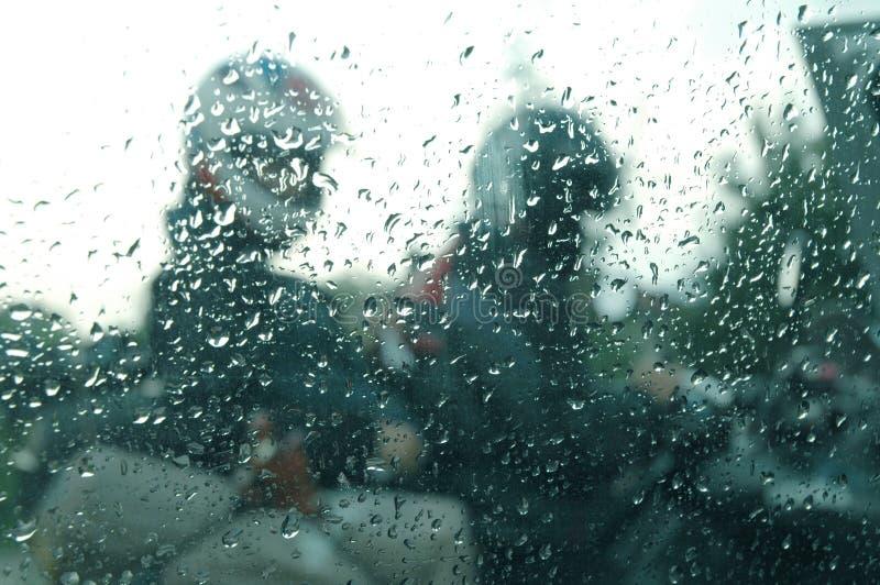 Motorrijders in de regen door een venster met regendalingen stock fotografie