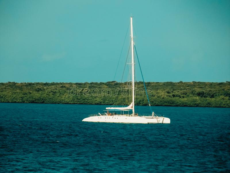 Motorsailer at anchor on steep green coast hill background. Luxury pleasure craft yacht with lowered sails on calm sea water. stock photography