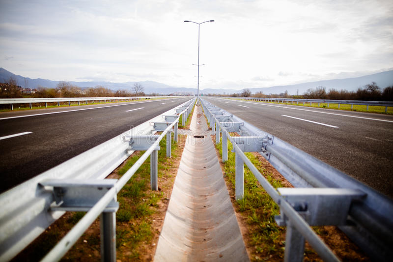 Motorväg på ängar för en ho för solig dag sceniska gröna Motorway som långdistans reser Asfalthuvudvägväg arkivfoto