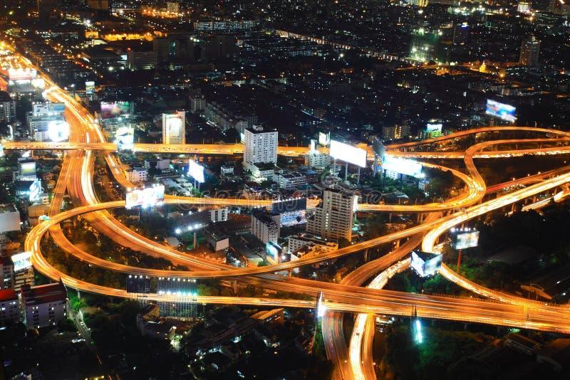 Motorvägen i natt med bilar tänder i modern stad royaltyfri foto