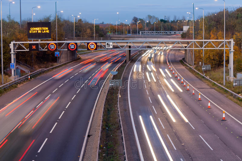 Motorway at dusk. M42 motorway traffic at dusk with congestion sign stock photography