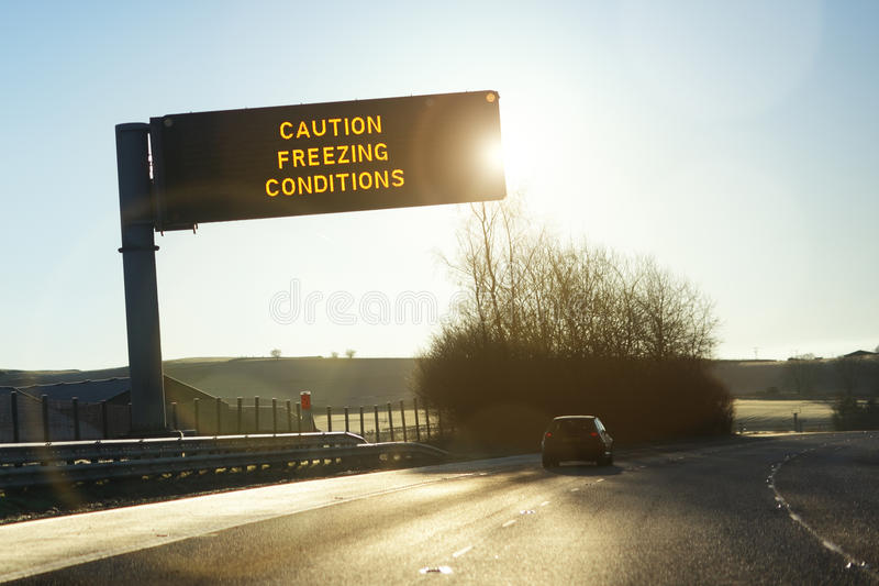 Motorway gantry sign in winter. Motorway gantry sign in early morning winter sunshine reading caution freezing conditions stock photos