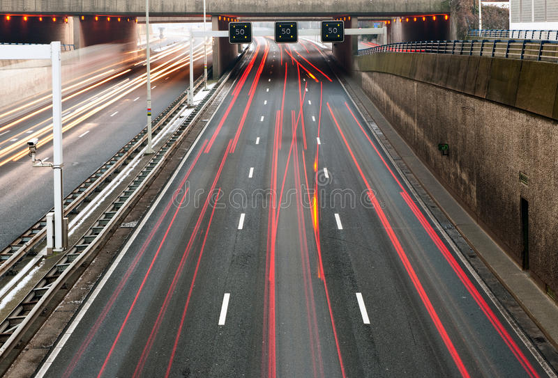 Motorway Information System. Indicating a speed limit and traffic jam ahead, with the trails of heavy traffic underneath stock image