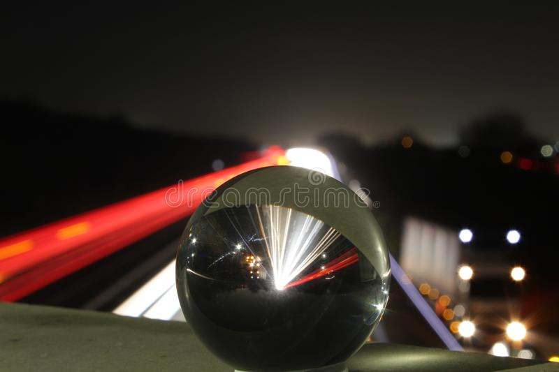 Motorway light trails with a glass sphere royalty free stock images