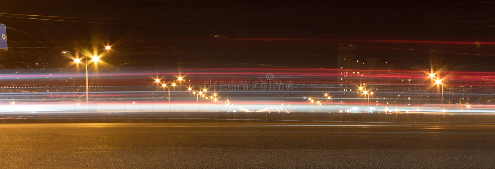 The motorway at night. The car moves at fast speed at the night. Blured road with lights with car on high speed. Panorama, banner royalty free stock photography