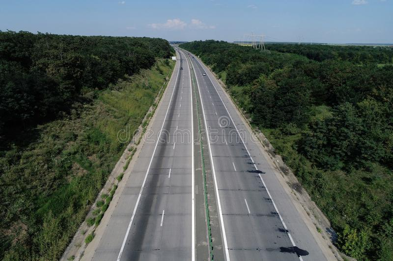 Motorway seen from above, green forest on both sides. Aerial view of highway, drone view stock photography