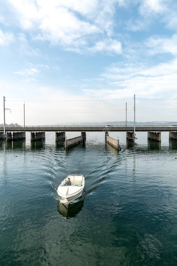 Motoscafo con i passaggi femminili di capitano dal più basso al lago superiore Zurigo attraverso il passaggio sul ponte di Seedam immagini stock libere da diritti