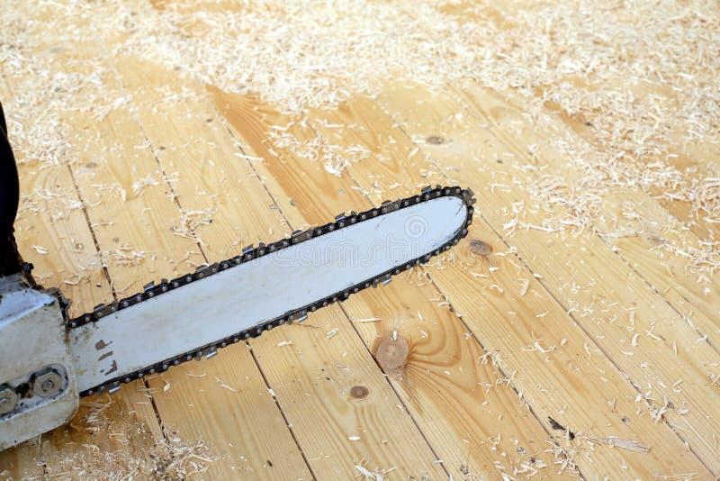 Motosierra para cortar la madera antes del serrín y de virutas imagen de archivo