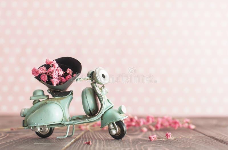 Mototrcycle azul do brinquedo do vintage com grupo de flores cor-de-rosa fotografia de stock royalty free