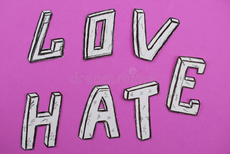 Mots écrits amour et haine, blancs sur un fond rose photographie stock