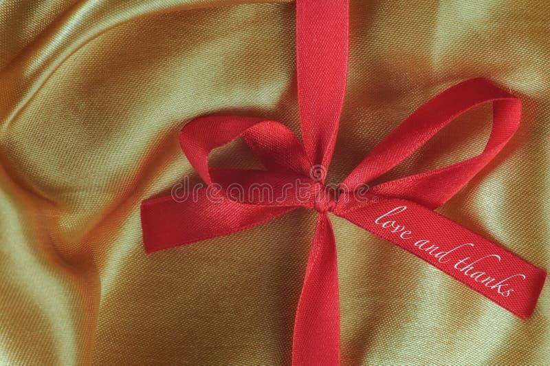 Mots d'amour et de mercis sur le ruban rouge photos stock