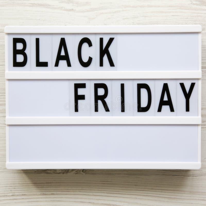 """Mots de """"Black Friday """"sur un conseil moderne sur un fond en bois blanc Configuration plate, a?rienne, d'en haut Plan rapproch? photographie stock libre de droits"""