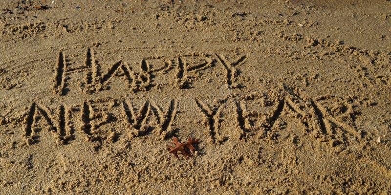 Mots de bonne année écrits en sable images stock