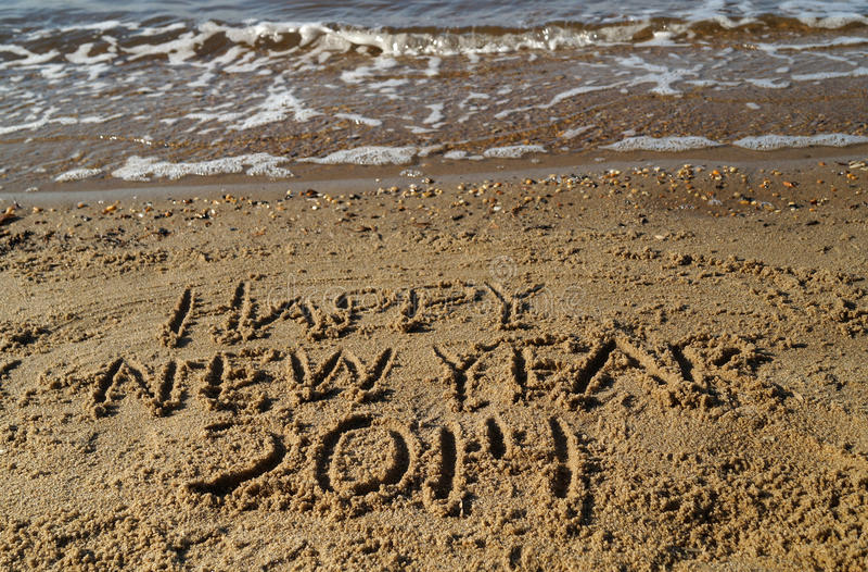 Mots de la bonne année 2014 écrits en sable photo stock