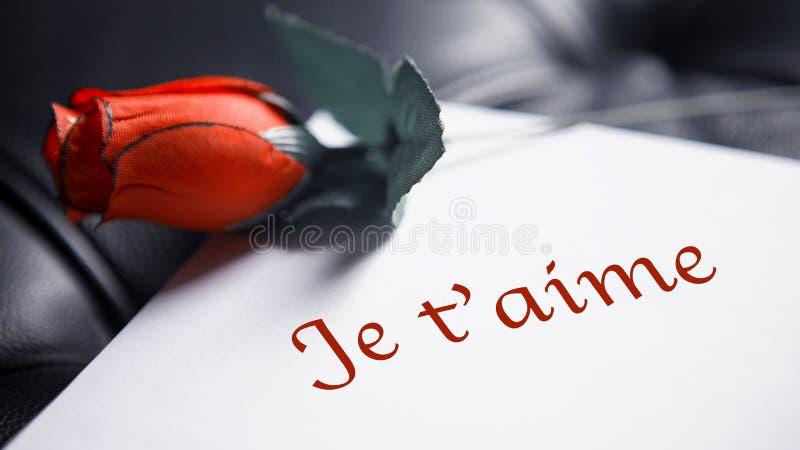 Mots français pour je t'aime sur le livre blanc avec la rose de rouge photos stock