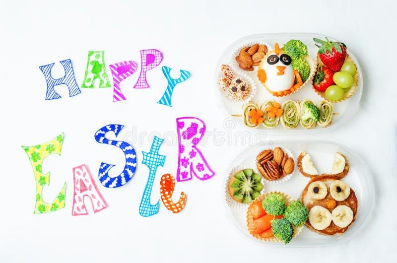 Mots heureux de Pâques avec des gamelles d'école pour des enfants photographie stock