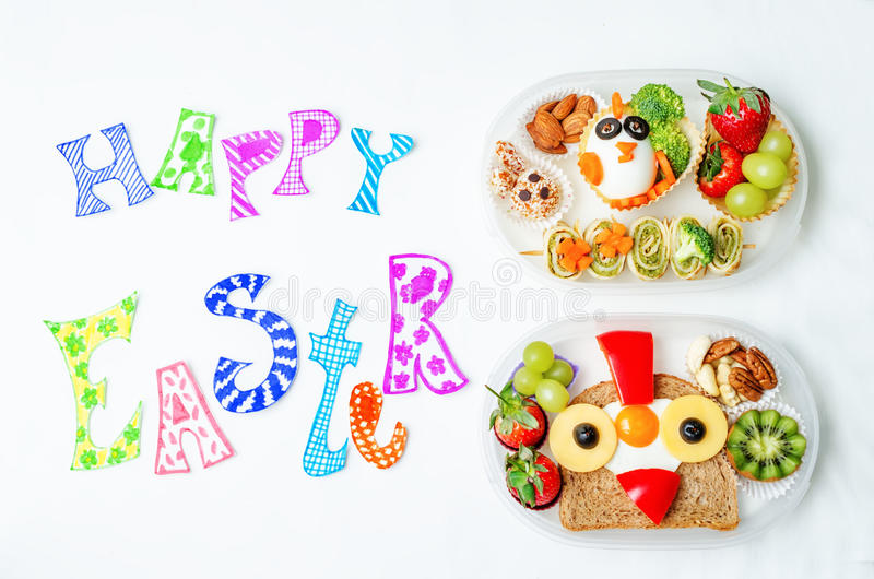 Mots heureux de Pâques avec des gamelles d'école pour des enfants avec la nourriture dedans images libres de droits