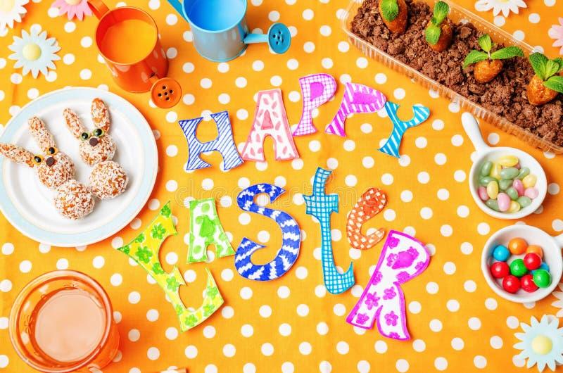 Mots heureux de Pâques avec les bonbons et le jus pour des enfants photographie stock
