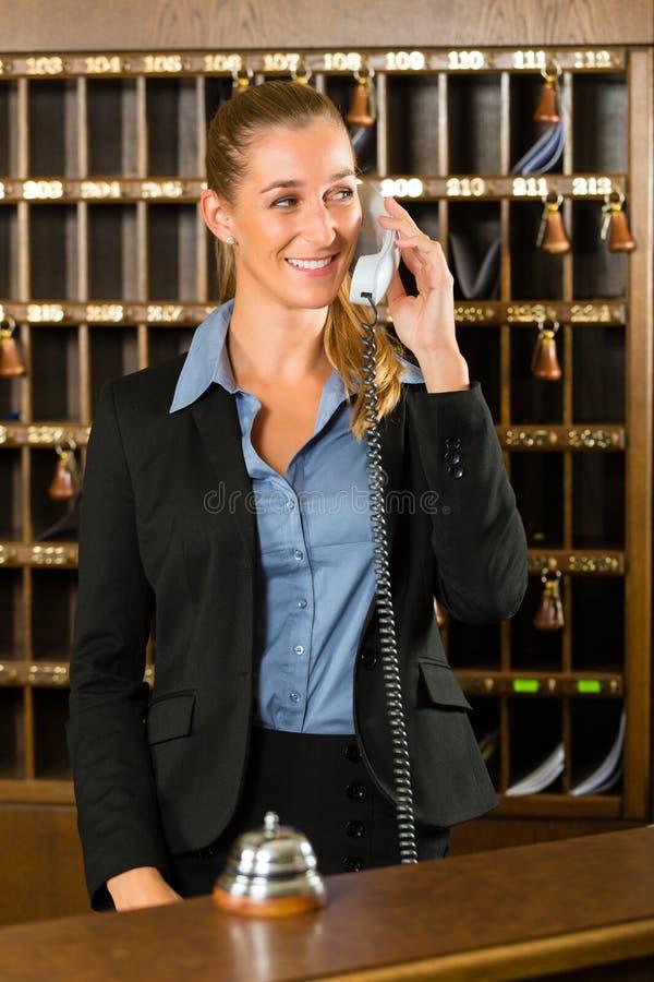 Mottagande av hotellet - skrivbordkontorist som tar en appell royaltyfri fotografi