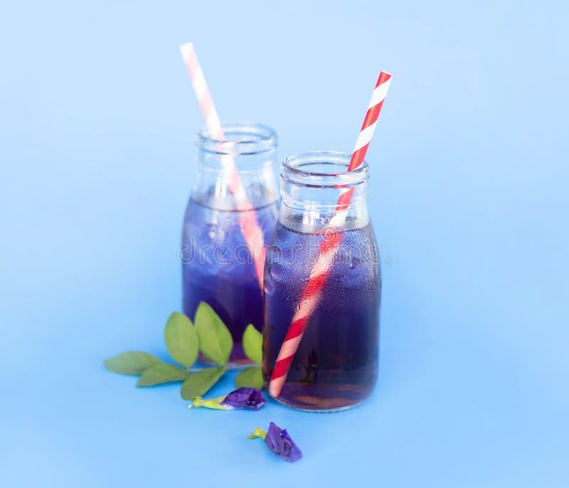 Motyliego grochu sok w trawy butelce z li?ciem i kwiatem na b?awym tle, zielarski dink dla zdrowego poj?cia zdjęcie stock