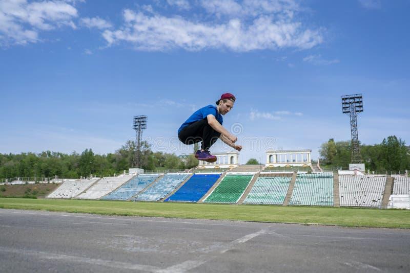 Mouche en hauteur de pratique en matière d'athlète de jeune homme dans le ciel au stade des jours d'un été photographie stock